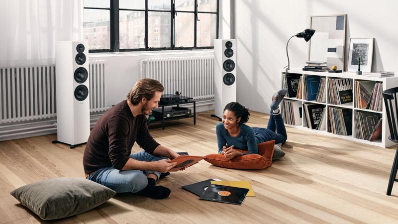 Dynaudio Emit højttalere og to mennesker på gulvet der smiler og lytter til musik